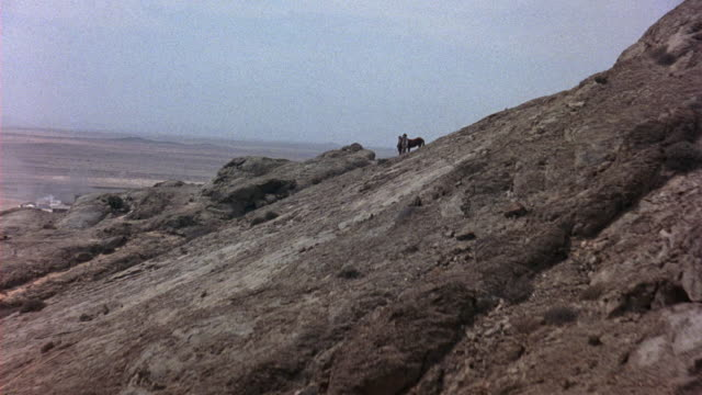 AERIAL OF BARREN HILLSIDE OF ROCKS AND DIRT. SEE BROWN HORSE STANDING ON CLIFF WITH A MAN DRESSED IN WESTERN STYLE CLOTHING. HE HOLDS THE REINS TO THE HORSE. SUNNY DAY. CAMERA CONTINUES PAST THE HILL OVER THE FLAT PLAINS.