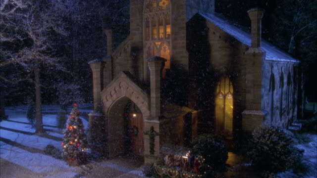 ZOOM IN WHILES SNOWING ON HISTORIC STYLE CHURCH WITH CHRISTMAS TREE AND LIGHTS IN FRONT. SNOW ON GROUND. ZOOMS IN TO DOOR, ENTRANCE, AND NATIVITY SCENE.