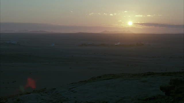 MEDIUM ANGLE OF LATE SUNRISE FROM DESERT HORIZON. SEE CLOUDS MOVE IN THE DISTANCE. SEE OUTLINE OF DARK CLOUDS AND MOUNTAINS IN BACKGROUND. SEE FAINT OUTLINES OF SHACKS OR BUILDING OF SMALL TOWN IN MID FOREGROUND.