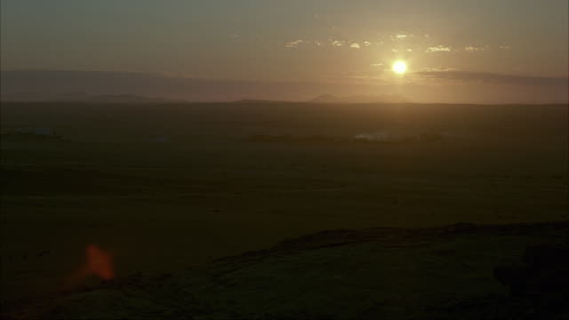 MEDIUM ANGLE OF SUNSET FROM DESERT HORIZON. SEE CLOUDS MOVE IN THE DISTANCE. SEE OUTLINE OF DARK CLOUDS AND MOUNTAINS IN BACKGROUND. SEE ROCKY STRUCTURE IN FOREGROUND UNDERNEATH POV.
