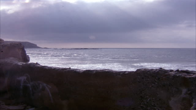 MEDIUM ANGLE OF ROCK WALL IN FOREGROUND BY SHORE WITH WAVES HITTING ON ROCK WALL. OCEAN HORIZON IN BACKGROUND. DARK CLOUDS IN SKY.