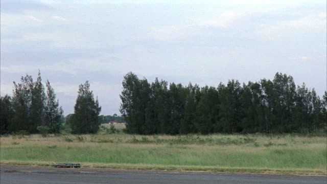 MEDIUM ANGLE OF AIRPORT RUNWAY. SEE GRASSY AREA NEXT TO RUNWAY. SEE THICK LINE ON TREES  AT EDGE OF FIELD. SEE POSSIBLE HOUSE IN FAR BACKGROUND. SEE THICK CLOUDS.