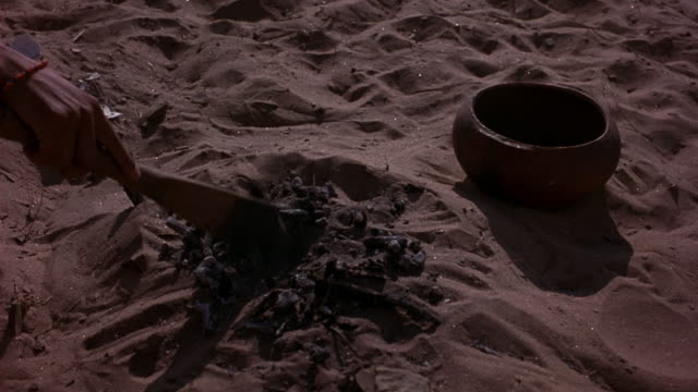 MEDIUM ANGLE OF SMALL MOUND CREATED FROM SAND. SEE STICKS, ROCKS, AND PIECES OF EGG SHELLS NEAR THE MOUND. A CLAY POT IS ALSO NEAR IT. SEE HAND HOLDING WOODEN COOKING PADDLE NUDGE STACK OF TWIGS AS SMOKE BEINGS TO RISE FROM THE HOT ROCKS IN THE PIT.