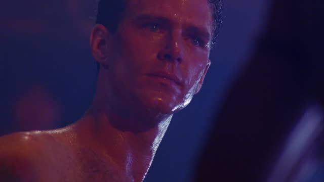 CLOSE ANGLE, UP ANGLE OF TWO SHIRTLESS MEN FIGHTING IN  BOXING RING. SEE FACE OF ONE SWEATING MAN AS HE IS KICKED IN FACE AND FALLS TO THE FLOOR.  SEE CROWD CHEER. ACTION.