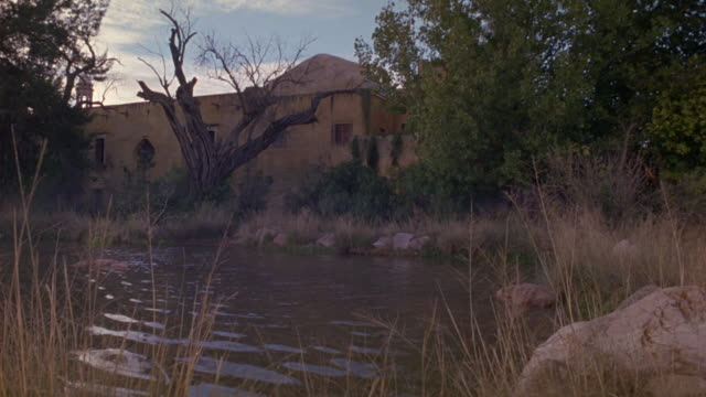 MEDIUM ANGLE OF SMALL LAKE OR PND IN RURAL ARID OR DESERT REGION. SEE ROCKS AND BRUSH IN THE FOREGROUND. SEE TWO-STORY HOUSE IN WITH GREEN VINES GROWING ON WALLS.