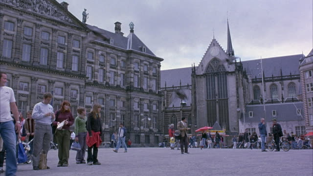 WIDE ANGLE OF DAM SQUARE. SEE ROYAL PALACE AND NIEUWE KERK CATHEDRAL. SEE TOURISTS AND PIGEONS IN SQUARE.