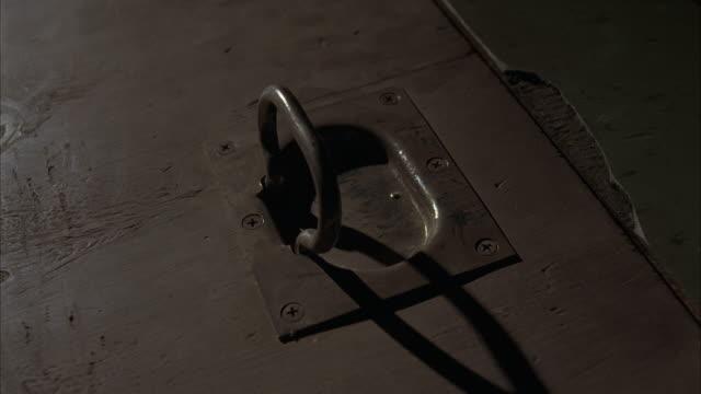 CLOSE ANGLE OF METAL TRAP DOOR HANDLE. HANDLE IS UP AS IF TRAP DOOR HAS BEEN RECENTLY ENTERED. TRAP DOOR IS WOOD.  FLOOR AROUND DOOR IS LINOLEUM AND CHIPPED.