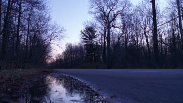 MEDIUM ANGLE OF SMALL ROAD IN COUNTRY. SEE BARE TREES ON BOTH SIDES, PROBABLY WINTER OR LATE FALL. BLACK FORD ESCORT DRIVES FROM RIGHT TO LEFT.