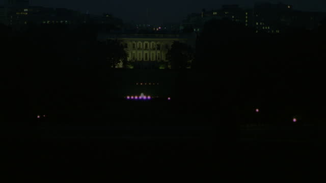 ESTABLISHED WIDE ANGLE OF WHITE HOUSE LIT AT NIGHT. FRONT YARD AND TREES SURROUND WHITE HOUSE. SEE LIGHTS ON TOP OF GATE IN FOREGROUND. OBSCURED BUILDINGS IN BACKGROUND.