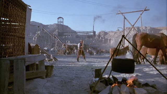 MEDIUM ANGLE OF DESERT MINING TOWN WITH BLACK KETTLE POT OVER OPEN FIRE. SEE MINERS WITH HORSES WALKING ACROSS FRAME. SEE TETHERED BROWN HORSES IN BACKGROUND. SEE VARIOUS MINING EQUIPMENT IN BACKGROUND.