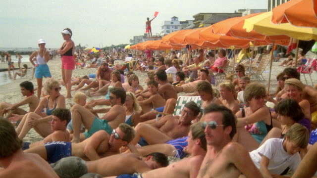 WIDE ANGLE OF SEVERAL PEOPLE LYING ON BEACH BELOW YELLOW AND ORANGE UMBRELLAS. SEE LIFEGUARD IN BACKGROUND WAVING FLAGS AND GIVING SIGNALS TO SOMEONE OFF SCREEN. SEE PEOPLE RUBBING SUNTAN LOTION ON OR LOOKING AT SOMETHING OFF SCREEN.
