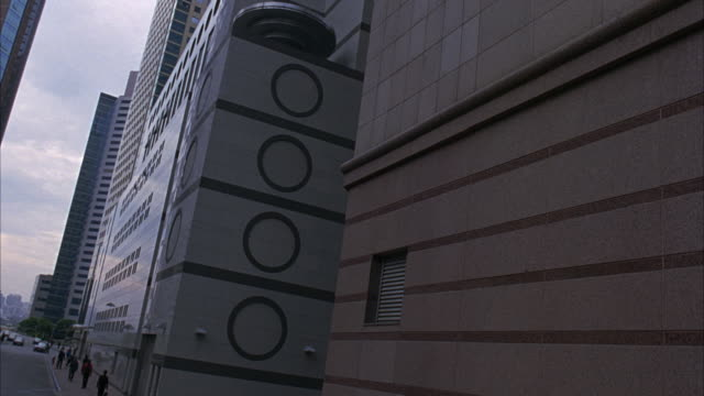 UP ANGLE OF FUTURISTIC SKYSCRAPERS OR OFFICE BUILDINGS SET IN THE CITY FROM MOVING POINT OF VIEW. SEE LARGE CIRCLES PAINTED ON SIDE OF ONE MULTI-STORY BUILDING. BUILDINGS HAVE BANDS OR ROWS OF REFLECTIVE WINDOWS. BUILDINGS ARE IN SHADOWS.