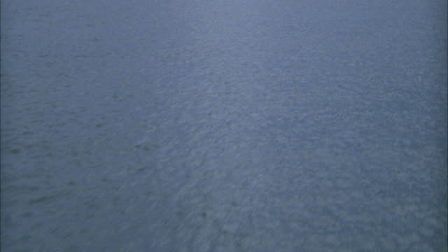 AERIAL OF OCEAN MOVING TOWARDS SHORE AND LAND. SEE MOUNTAIN IN BACKGROUND. POSSIBLE POV PERSON ON BOAT.