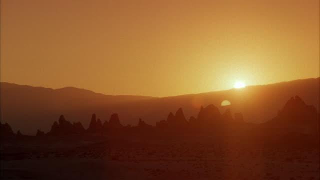 WIDE ANGLE OF DESERT AT SUNSET. SEE JET FLY ACROSS SHOT. TRONA PINNACLES. MOJAVE DESERT, CALIFORNIA