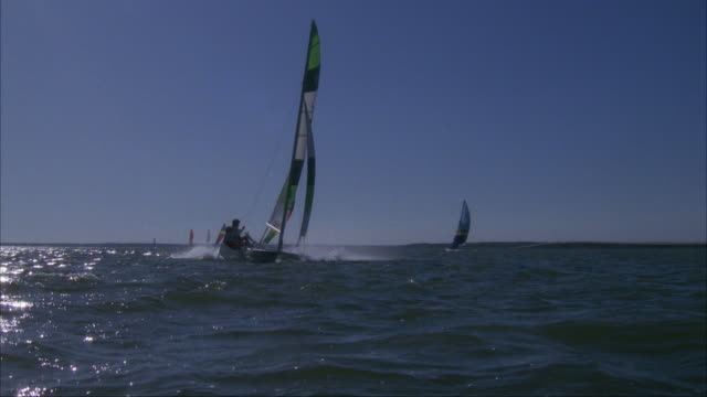 MEDIUM ANGLE OF HANDFUL OF CATAMARANS SAIL TO RIGHT. MOST LIKELY DURING RACE, CATAMARANS TILT AS PEOPLE LEAN BACK AND ADJUST SAIL TO WIND. CATAMARANS EXIT FRAME TO RIGHT.