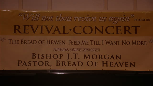 WIDE ANGLE OF BANNER, POSTER, OR SIGN IN CHURCH, COMMUNITY CENTER, OR RELIGIOUS BUILDING. SIGN READS REVIVAL CONCERT, THE BREAD OF HEAVEN, FEED ME TILL I WANT NO MORE AND SPECIAL GUEST SPEAKER BISHOP J.T. MORGAN, PASTOR, BREAD OF HEAVEN.