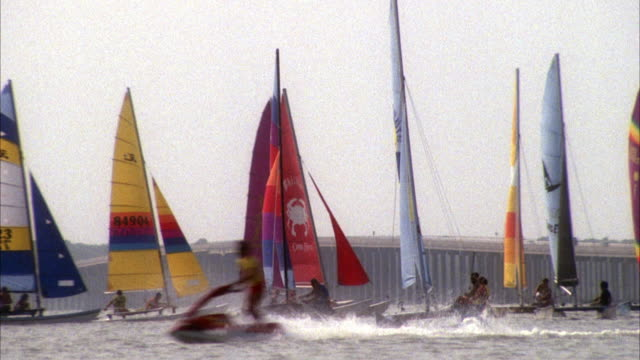 MEDIUM ANGLE OF HANDFUL OF CATAMARANS SAIL IN OCEAN. MOST LIKELY DURING RACE. SEE ROAD IN FAR BACKGROUND.