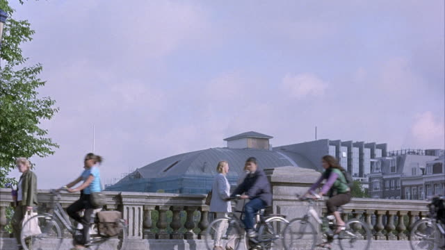 MEDIUM ANGLE OF PEDESTRIANS AND BICYCLES ON SIDEWALK OF BRIDGE, LEFT AND RIGHT. EUROPEAN ARCHITECTURE IN BACKGROUND.