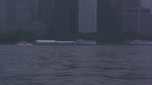 WIDE ANGLE ON THE NEW YORK CITY SKYLINE VIEWED FROM A BOAT. CAMERA ROCKS ON BOAT.
