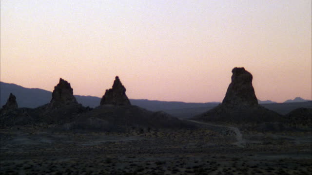 ESTABLISHED MEDIUM ANGLE OF THREE MOUNTAIN SPIRES OR ROCK FORMATIONS IN DESERT. SHRUBS AND SMALL HILL IN FOREGROUND AND BACKGROUND. TRONA PINNACLES, MOJAVE DESERT CALIFORNIA.