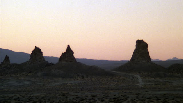 ESTABLISHED MEDIUM ANGLE OF THREE MOUNTAIN SPIRES OR ROCK FORMATIONS IN DESERT. SHRUBS AND SMALL HILL IN FOREGROUND AND BACKGROUND. TRONA PINNACLES, MOJAVE DESERT, CALIFORNIA