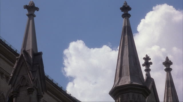 UP ANGLE OF STEEPLES OR SPIRES ON CHURCH OR CATHEDRAL. WHITE CLOUDS GO BY IN BACKGROUND.