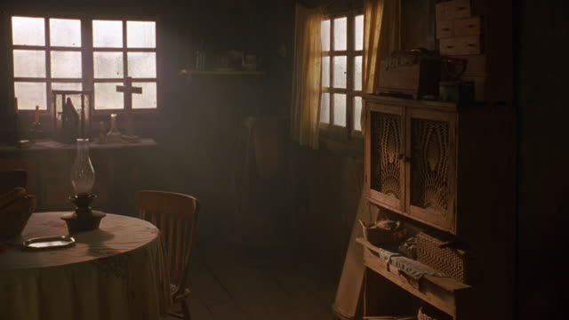 MEDIUM ANGLE OF FRONT ROOM, OR DINING ROOM IN HOUSE. HOUSE IS WORN OR RUSTY. SEE WOODEN CHAIRS AND CUPBOARD IN FOREGROUND. SEE FOGGED WINDOWS. SEE LANTERN ON TABLE. SEE WOODEN CROSS ON TABLE IN BACKGROUND.