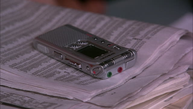EST CLOSE ANGLE OF ELECTRONIC DEVICE, COULD BE RECORDER OR DIGITAL CAMERA LYING ON TOP OF BUSINESS SECTION OF NEWSPAPERS.