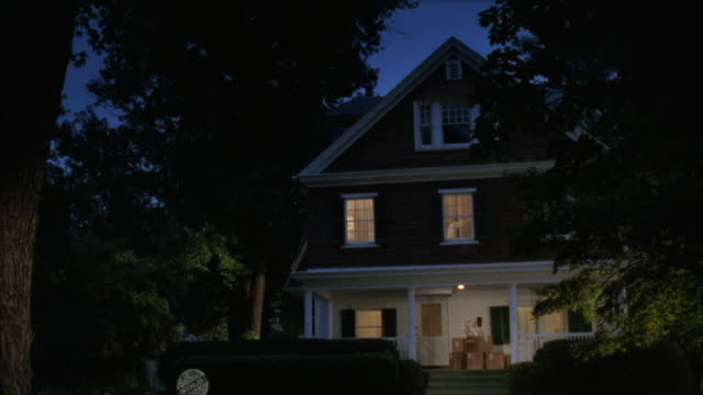 MEDIUM ANGLE OF TWO STORY MIDDLE CLASS HOME IN SUBURBS. SEE HAND IN FRONT OF CAMERA IN MIDDLE OF SHOT FOR APPROXIMATELY TWO SECONDS