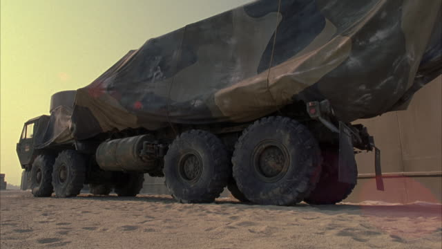 MEDIUM ANGLE OF TARP COVERED ARMY TRUCK. SIDE REAR ANGLE. SHOT PULLS BACK AS TRUCK DRIVES FROM RIGHT TO LEFT OUT OF SHOT. SEE TWO MEN IN ARMY UNIFORMS IN FOREGROUND.
