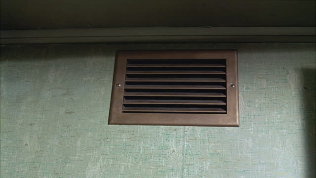 CLOSE ANGLE OF METAL HEATING VENT COVER NEAR CEILING IN LOWER CLASS MOTEL OR HOTEL ROOM OR APARTMENT. GRATE, DUCT, HVAC.