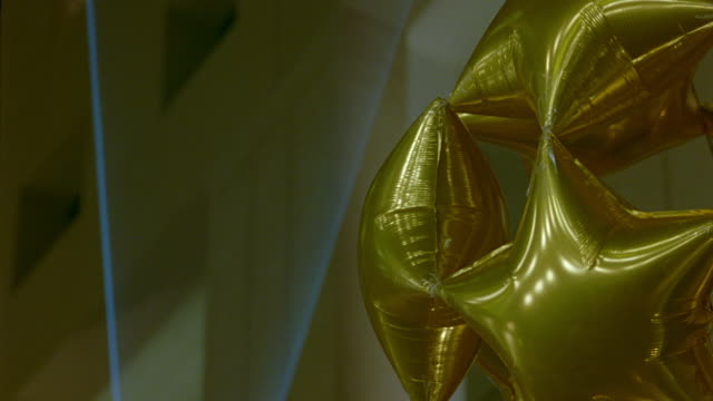 MEDIUM ANGLE OF LARGE BUNDLE OF GOLD STAR-SHAPED BALLOONS ATTACHED IN THE SHAPE OF A SPHERE. TO FRAME LEFT SEE BLUE LIGHTS OR BEAMS ILLUMINATE ON WALL.