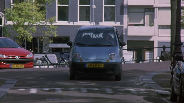 MEDIUM ANGLE OF FRONT OF BLUE HATCHBACK FACING POV. HATCHBACK STOPPED AT CROSSWALK ON SIDE STREET IN AMSTERDAM. EUROPEAN STRUCTURE IN BACKGROUND.