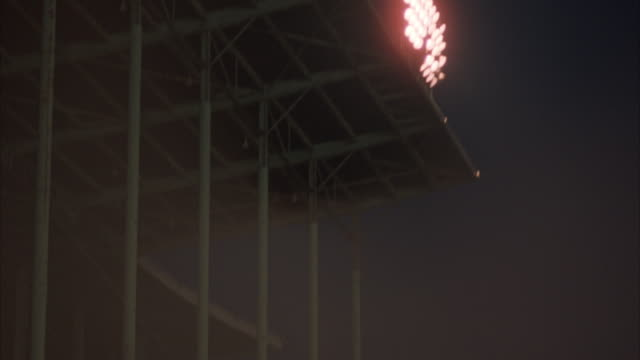 MEDIUM UP ANGLE OF STADIUM SUPPORTING POLES. SEE SIDE ANGLE SHOT OF CEILING ON STADIUM BEING HELD UP BY POLES. SEE FLASHES OF LIGHT OF BACKGROUND THAT COULD BE LIGHTNING. SHOT PANS UP, SEE STADIUM LIGHTS ATOP STADIUM. POV FROM UNDER OVERHANG OF STADIUM.