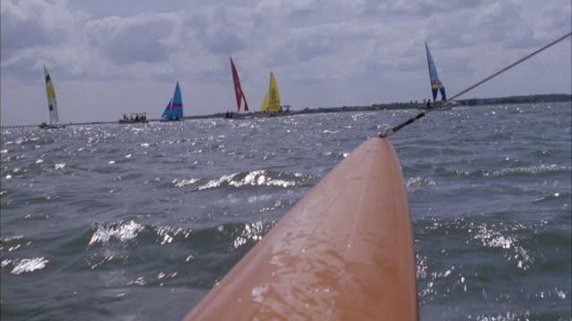MEDIUM ANGLE MOVING POV ON SAILBOAT. SEE HANDFUL OF SAILBOATS AHEAD SAILING ON OCEAN, SAILBOAT BOW IN FOREGROUND.