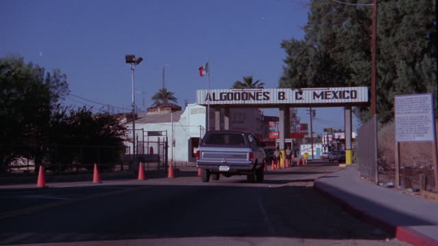 WIDE ANGLE OF BORDER CROSSING INTO MEXICO. ORANGE CONES LEAD TO CROSSING. SIGN READS ALGODONES B.C. MEXICO. BORDER AGENTS IN BACKGROUND. A TRUCK APPROACHES CROSSING AND STOPS BEFORE PASSING THROUGH. BORDER TOWNS.