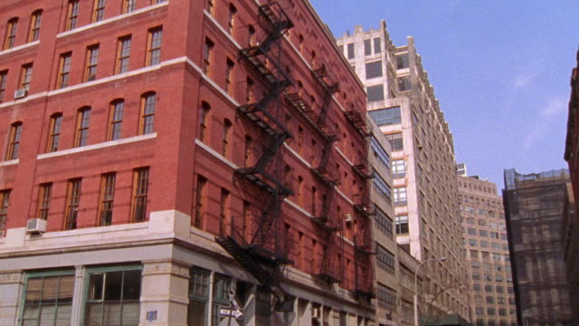 WIDE ANGLE OF A BRICK BUILDING, PROBABLY AN APARTMENT BUILDING, OFFICE BUILDING, OR LOFT.  SEVERAL FIRE ESCAPES ON THE SIDE. COULD BE UPPER CLASS OR MIDDLE CLASS. SEE OTHER MATCHING ANGLES ON THIS TAPE.