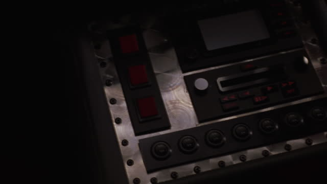 CLOSE ANGLE OF RADIO CONSOLE WITH BUTTONS, TAPE DECK OR DISK DRIVE AND DIGITAL DISPLAY SCREEN MOUNTED IN MOVING CAR. SUGGESTS CUSTOMIZED OR FUTURISTIC CAR. FINGER PUSHES BUTTONS. DISC. MINIDISC.