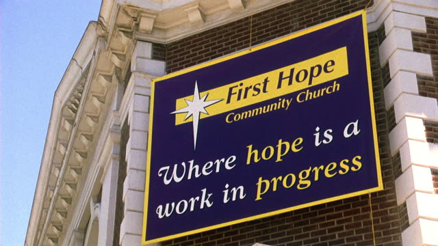 UP ANGLE OF BANNER ON CORNER OF BRICK BUILDING THAT READS FIRST HOPE COMMUNITY CHURCH, WHERE HOPE IS A WORK IN PROGRESS. CHURCH, CHAPEL, COMMUNITY CENTER, OR OTHER RELIGIOUS BUILDING.