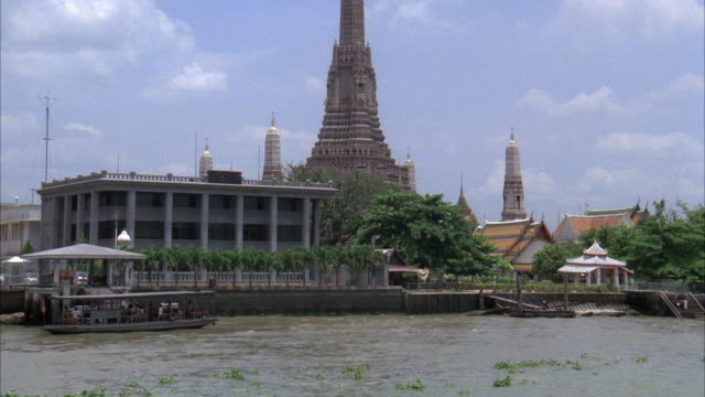 MEDIUM ANGLE MOVING POV FROM RIVER LOOKING AT BUILDINGS ON SHORE. SEE LARGE TEMPLE WITH SPIRES. SEE RIVER IN FOREGROUND.
