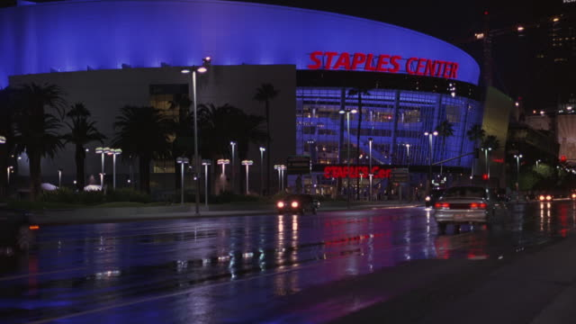 PAN RIGHT TO LEFT AS AN SUV CAR DRIVES PAST THE STAPLES CENTER BASKETBALL ARENA OR STADIUM IN DOWNTOWN LOS ANGELES. ALSO USED AS A CONCERT HALL OR VENUE. THE CAR ALSO PASSES THE CONVENTION CENTER.