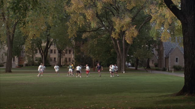 MEDIUM ANGLE OF MEN PLAYING FOOTBALL ON COLLEGE CAMPUS. QUARTERBACK THROWS BALL OUT OF FRAME TO LEFT, MEN WALK BACK SLOWLY TOWARDS CENTER AT END.