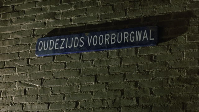 MEDIUM ANGLE OF SIGN THAT SAYS OUDEZIJDS VOORBURGWAL. AMSTERDAM COFFEE SHOP. SIGN POSTED ON BRICK WALL.