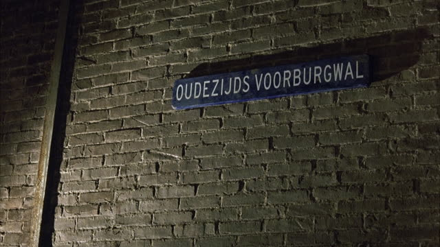 PAN UP OF SIGN THAT SAYS OUDEZIJDS VOORBURGWAL. AMSTERDAM COFFEE SHOP. SIGN POSTED ON BRICK WALL.