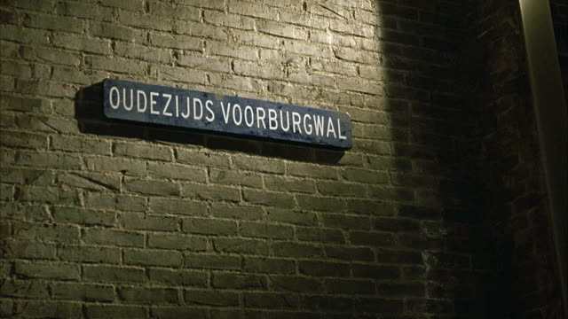 MEDIUM ANGLE OF SIGN THAT SAYS OUDEZIJDS VOORBURGWAL. AMSTERDAM COFFEE SHOP. SIGN POSTED ON BRICK WALL. SHAKY SHOT.
