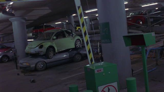 MEDIUM ANGLE OF GREEN VOLKSWAGEN BEETLE OR BUG CAR SITTING ON TOP OF BLUE FORD SEDAN INSIDE OF PARKING GARAGE OR STRUCTURE. BOTH CARS APPEAR SMASHED AND DAMAGED.