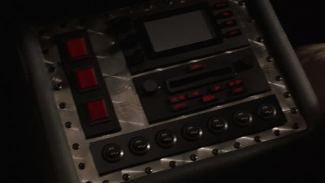 CLOSE ANGLE OF RADIO CONSOLE WITH BUTTONS, TAPE DECK OR DISK DRIVE AND DIGITAL DISPLAY SCREEN MOUNTED IN MOVING CAR. SUGGESTS CUSTOMIZED OR FUTURISTIC CAR. DISC. MINIDISC.