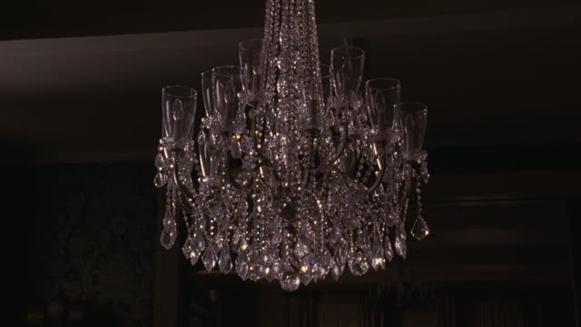 MEDIUM ANGLE OF  A CHANDELIER HANGING IN FRONT OF A DOORWAY.  COULD BE A LIVING ROOM OR DINING ROOM IN A HOME.  THE GLASS BREAKS AND SHATTERS FROM WHAT COULD BE A GUNSHOT OR A HIGH PITCH SOUND.   40FPS