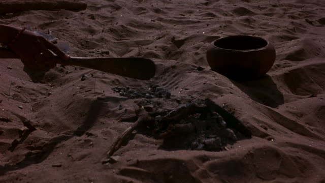 MEDIUM ANGLE OF SMALL MOUND CREATED FROM SAND. SEE STICKS, ROCKS, AND PIECES OF SEASHELLS NEAR THE MOUND. A CLAY POT IS ALSO NEAR IT.
