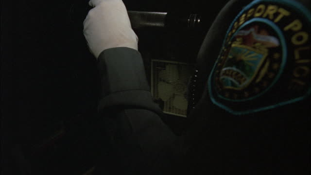 CLOSE ANGLE OF BRIDGEPORT POLICE OFFICER'S ARM AND SHOULDER AS HE SEARCHES HOME OFFICE. OPEN DESK DOOR CONTAINS KETCHUP AND TACO SAUCE PACKETS. HE IS WEARING LATEX GLOVES AND HOLDING FLASHLIGHT.